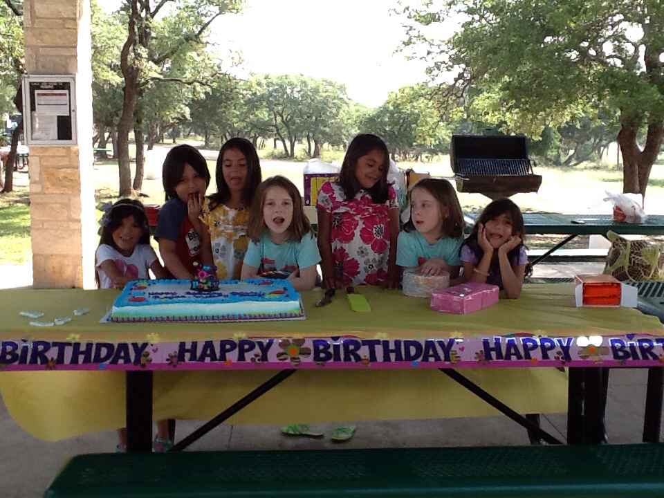 3 sets of identical twins and a little boy pose over a birthday cake