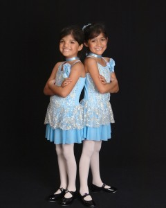 M and J, posed back to back in matching dance costumes,