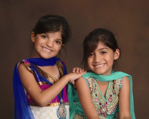 J and M are both wearing South Asian attire, but in different styles and colours.