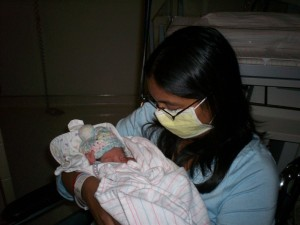 Sadia wearing a surgical mask and holding J.