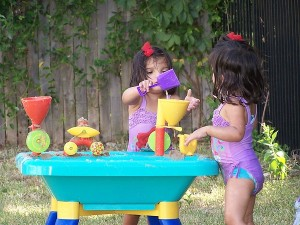 Twins playing with a sand and water table from hdydi.com