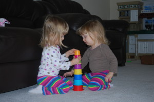 Cooperating to make a tower at two years old.