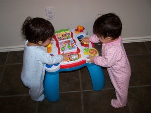 Twins playing together with an activity table from hdydi.com