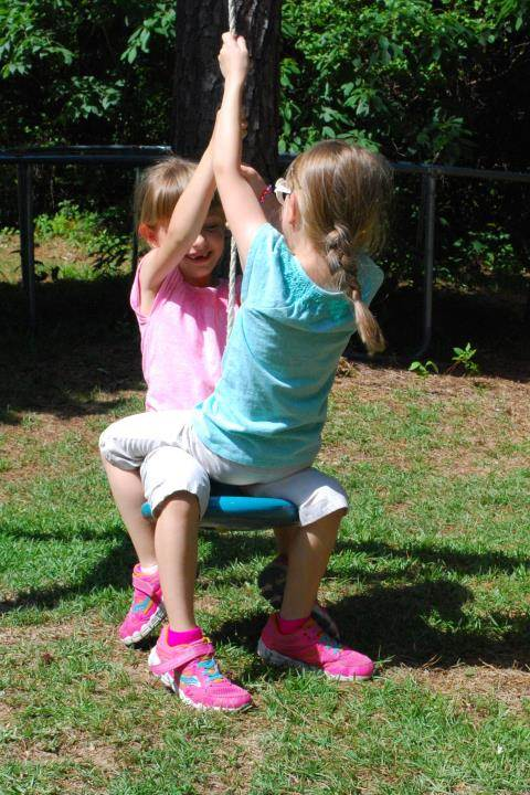 Too big for a bucket swing, perhaps, but these twin sisters are never too big for an outdoor adventure.