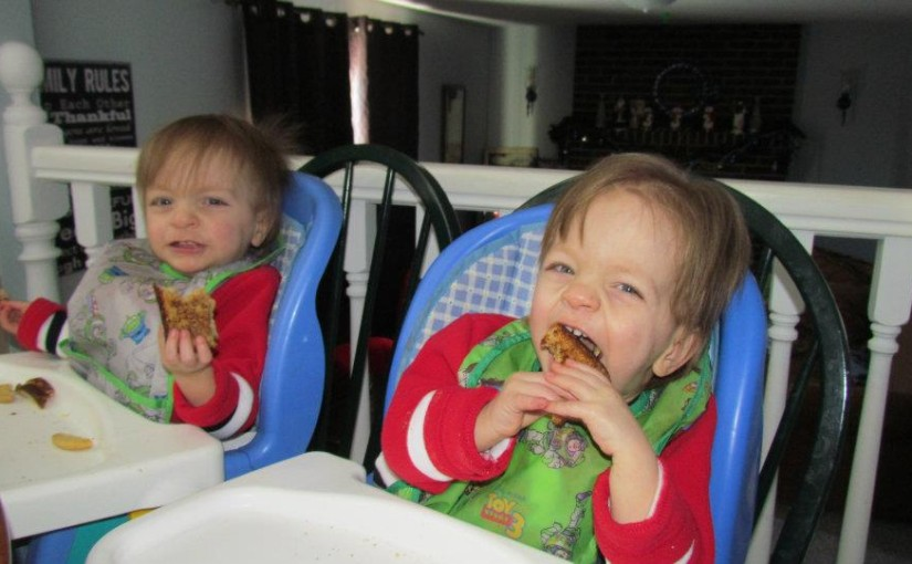 Toddler twins in high chairs